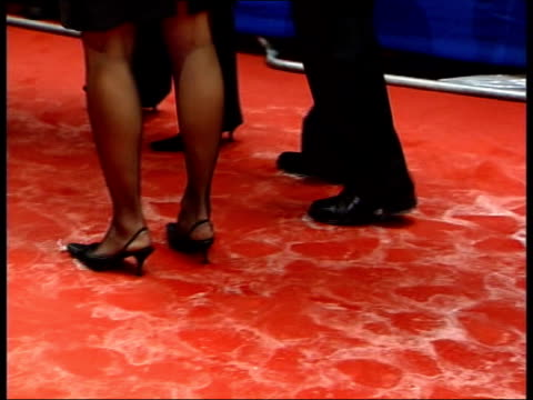 awards ceremony; itn england: london: ext open sandals of celebrity along wet carpet sodden red carpet as feet of people along actor david jason and... - ricky gervais stock videos & royalty-free footage