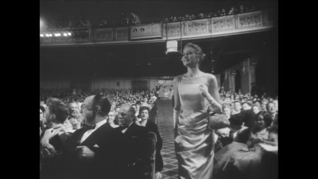 Awards show a the RKO Pantages Theatre / Oscar statue / audience clapping / Grace Kelly walks down aisle and to stage to accept Oscar for Best...
