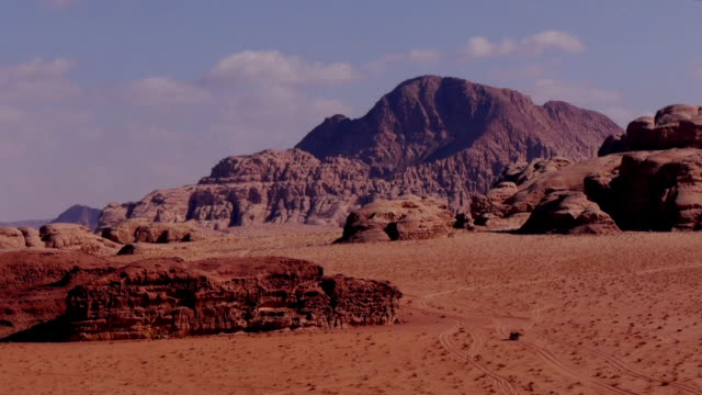 Awesome desert scenery with a Jeep passing in Wadi Rum, Jordan, Middle East.
