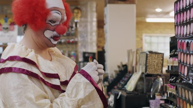 vidéos et rushes de awkward clown shopping for lipstick in store / pleasant grove, utah, united states - rouge à lèvres rouge