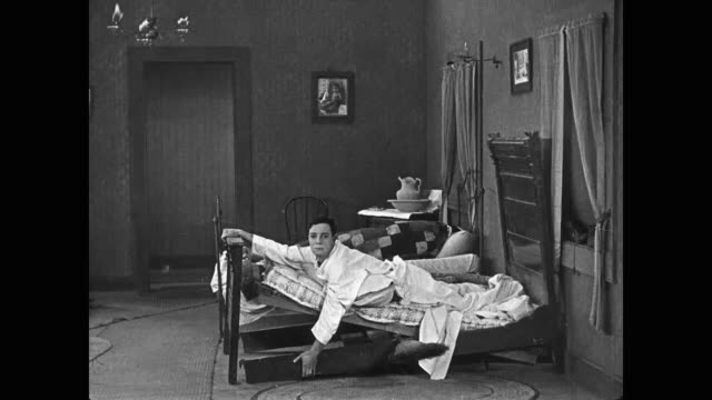 1922 Awkward man (Buster Keaton) places mattress on top of angry woman before struggling to maintain balance in his own bed