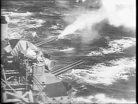 axis fighter plane crashes into sea between british convoy ships / crashed plane burning at sea / montage of battle with british antiaircraft guns... - convoy stock videos & royalty-free footage
