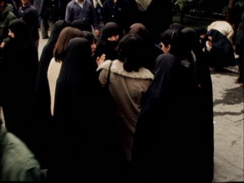 Ayatollah calls for Islamic Republic IRAN Tehran EXT People in street Bazaar / Man with carpet at market stall TILT as one counts money / Iranian...
