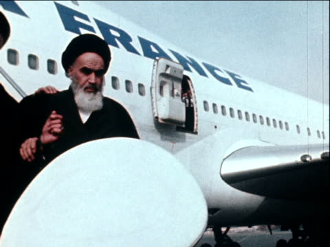 vidéos et rushes de ayatollah ruhollah khomeini descends aeroplane steps and is surrounded by crowd of supporters on his return to iran after 15 years in exile 1... - 1979