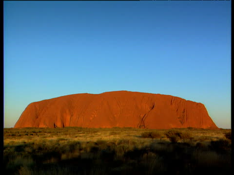 ayers rock (uluru) changing from day to night green grassy bush land in foreground - エアーズロック点の映像素材/bロール