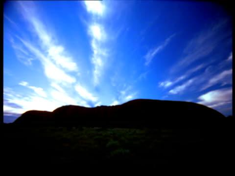 Ayers Rock lies in silhouette beneath a vivid blue sky.