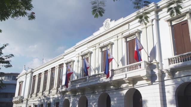 ayuntamiento de manila at intramuros. iconic colonial style building from philippines spanish occupation. philippines national flag - colonial stock videos & royalty-free footage