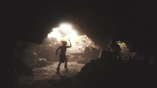 Azecs Dancing and playing drums inside a cave