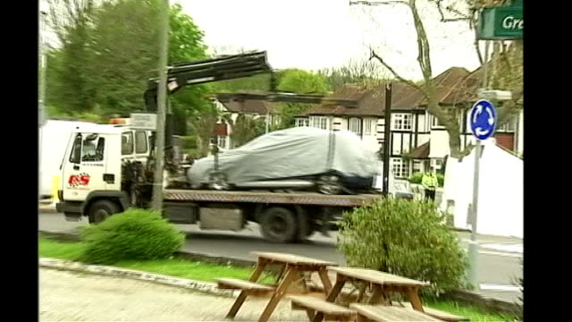 azelle rodney shooting inquiry; tx 1-2.5.2005 edgware: tow truck carrying tarpaulin covered car along and past various of man securing car to tow... - 防水シート点の映像素材/bロール