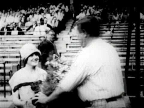 stockvideo's en b-roll-footage met babe ruth bringing sister mamie bouquet of flowers in ballpark / newsreel - 1927