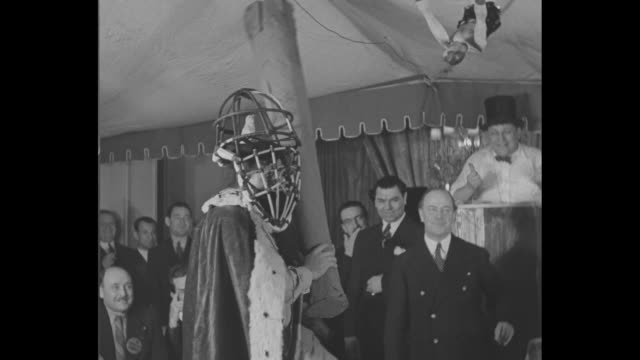 babe ruth dressed in robe, crown, wig, beard and face cage, takes swing with giant fake bat / tony sarg, president of circus saints and sinners club,... - gabbia di battuta video stock e b–roll