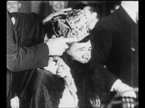 babe ruth in cowboy costume sits on top of limousine with longhorns on front and grabs horns as if riding a bronco / hands put crown on ruth's head... - hands behind head stock videos and b-roll footage
