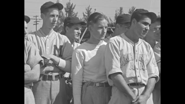 Babe Ruth in NY Giants uniform instructs teenage baseball student on proper throwing technique / group of students look on / VS Ruth instructing...