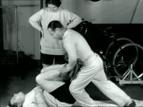 vídeos y material grabado en eventos de stock de babe ruth lying on floor doing exercises with trainer in gym / documentary - 1926