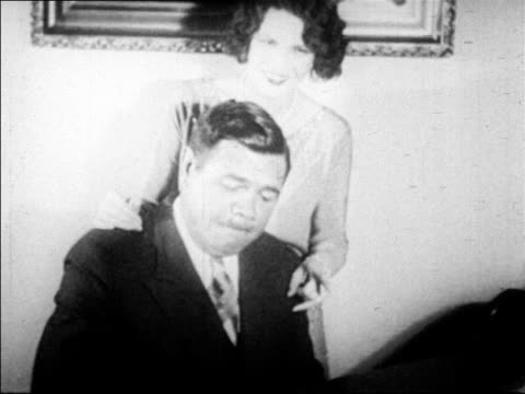 stockvideo's en b-roll-footage met babe ruth playing piano smiling as wife claire stands behind him / newsreel - 1927