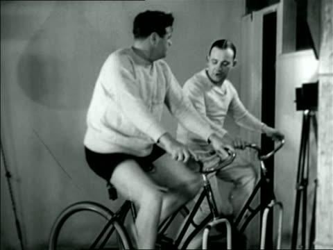 vídeos y material grabado en eventos de stock de babe ruth riding exercise bicycle with other man / documentary - 1926
