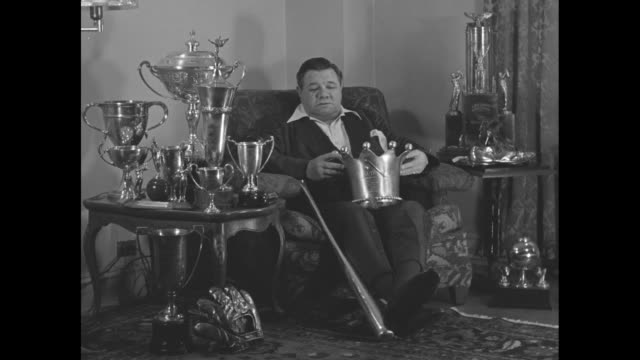 WS Babe Ruth sits in armchair wearing a smoking jacket and smoking a pipe surrounded by trophies he has a large metal crown in his lap and a baseball...