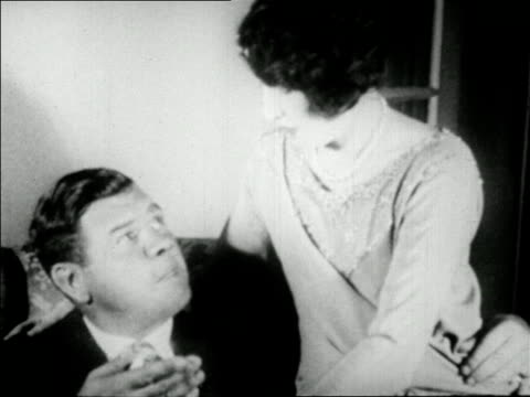 stockvideo's en b-roll-footage met babe ruth sitting in chair kissing second wife claire hodgson ruth / newsreel - 1927