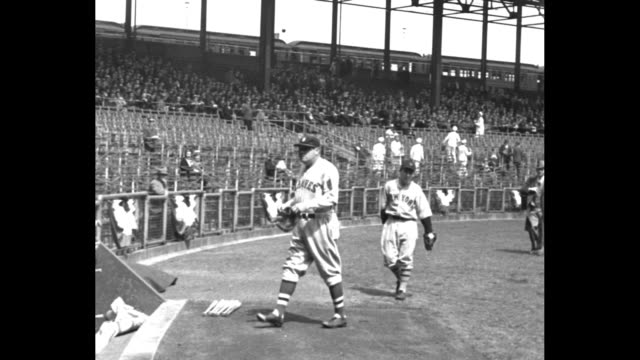 Babe Ruth wearing Boston Braves uniform walks across field towards stands / he shakes hands with Colonel Jacob Ruppert owner of NY Yankees standing...