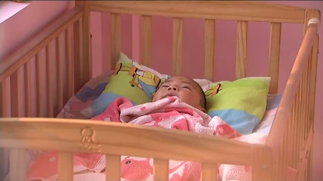 stockvideo's en b-roll-footage met babies abandoned at 'baby hatches' china eastern china ext sequence mother carries her baby to 'baby hatch' leaves baby in cot in entrance hall and... - hatch