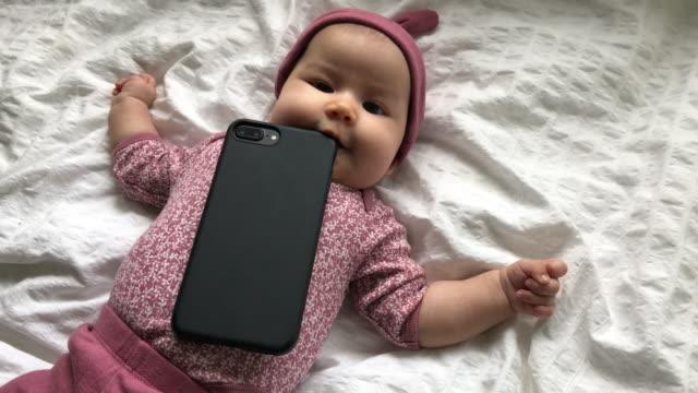vídeos de stock e filmes b-roll de babies ruining smartphones - mastigar