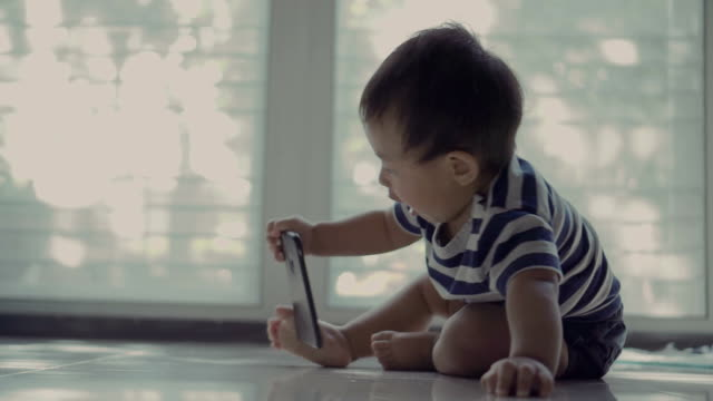 babies ruining smartphones - curiosità video stock e b–roll