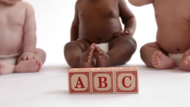 Babies sitting by blocks spelling ABC