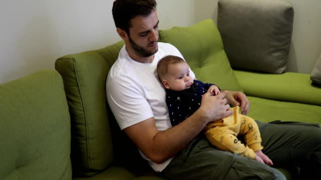 vidéos et rushes de bébé et papa, regarder la télévision sur le canapé - genderblend