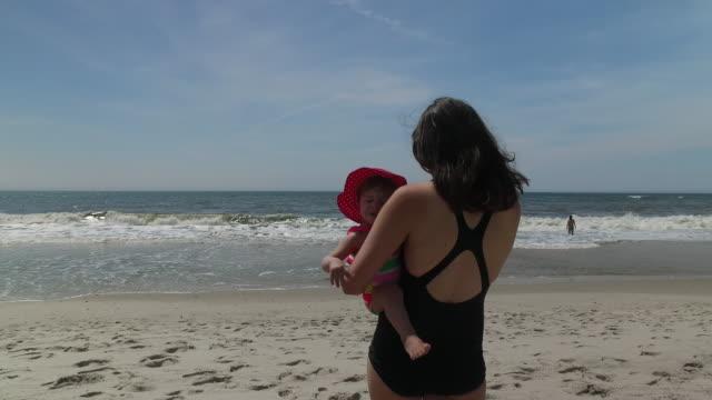 Baby and her mother playing in the sand at the ocean beach on a summer day, 4K stabilized footage