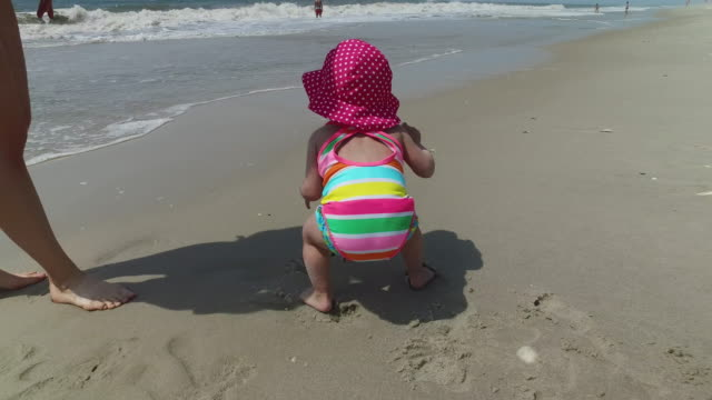 baby and her mother playing in the sand at the ocean beach on a summer day, 4k stabilized footage - one piece swimsuit stock videos and b-roll footage
