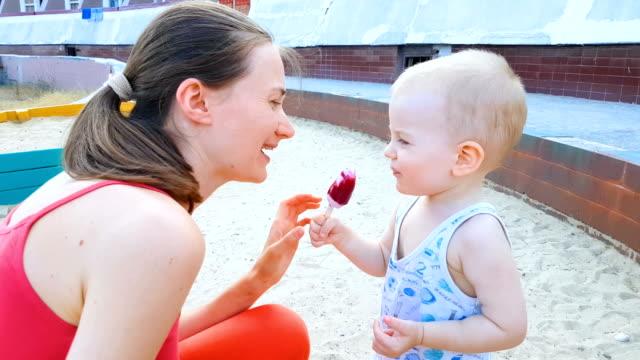 vídeos y material grabado en eventos de stock de bebé y la mamá comer helado en el parque - antihigiénico