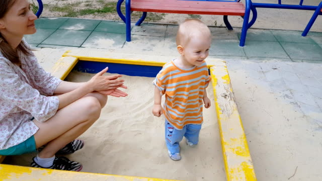 Baby and mom playing in sandbox