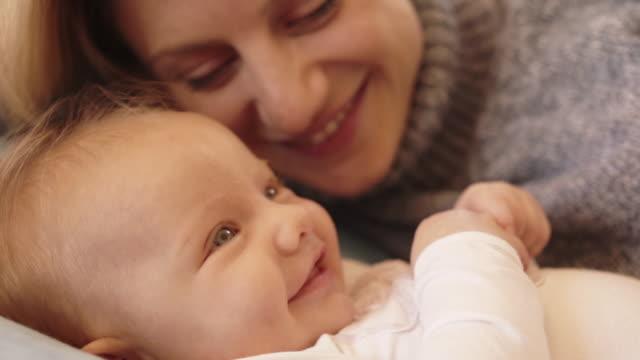 baby and mother lying on sofa. - 生後2ヶ月から5ヶ月点の映像素材/bロール