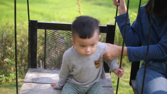 baby and mother playing swing - gold rush stock videos and b-roll footage