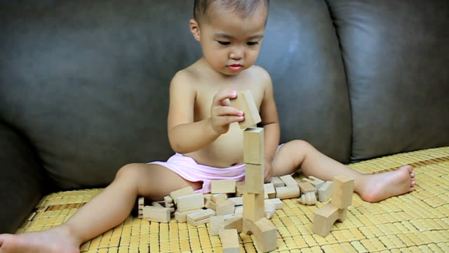 baby applaud after building blocks,hit them down,laugh deliberately.