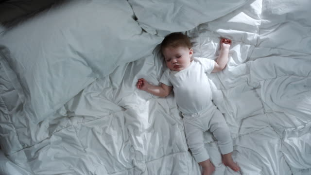 baby asleep on a big bed