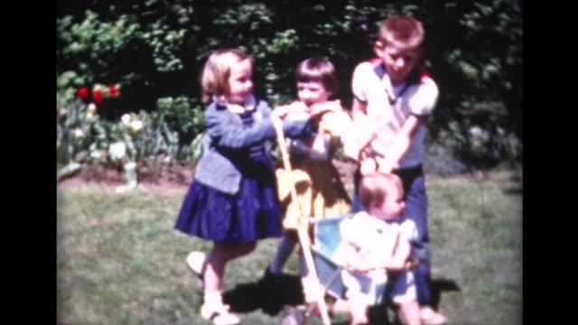 vídeos de stock, filmes e b-roll de 1961 baby being pushed around in stroller - roupa de bebê