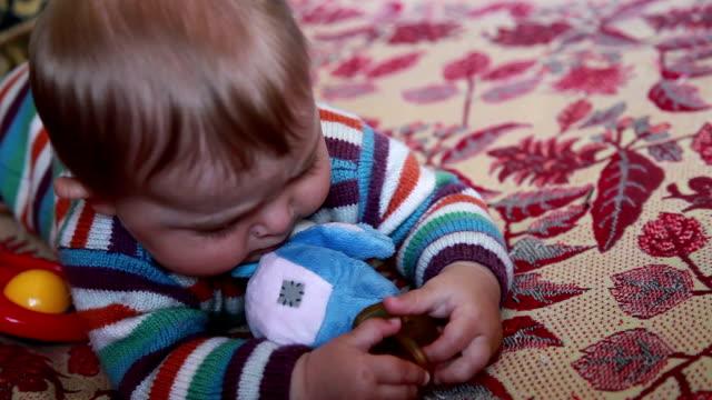Baby biting pacifier in her hands