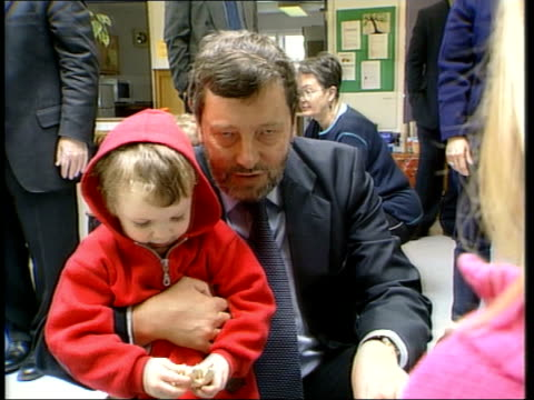 Baby bond plans announced by government BV David Blunkett kneeling beside children in nursery as children stroke his guide dog Young child in nursery...