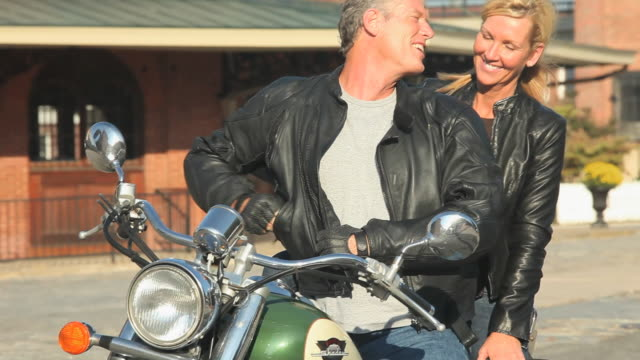 ms tu baby boomer couple sitting on motorcycle, man using mobile phone, petersburg, virginia, usa - leather jacket stock videos and b-roll footage
