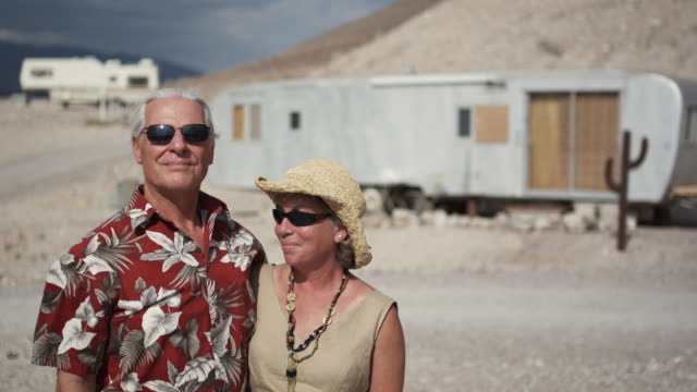 ms baby boomer hippie couple with sunglasses standing near trailer in desert / tecopa, california, usa - sunglasses stock videos & royalty-free footage