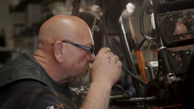 baby boomer man working on motorcycle - ゴーティー点の映像素材/bロール