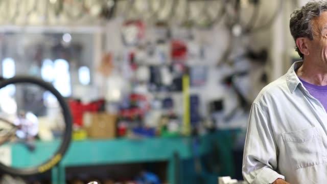 vidéos et rushes de baby boomer owner of bike shop - téléphone sans fil
