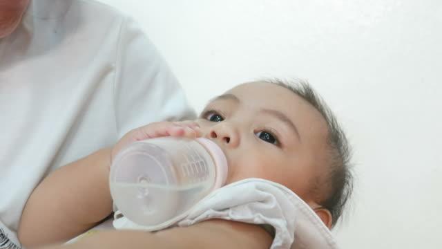 Baby füttern mit der Flasche und auf Mutter Schoß liegend