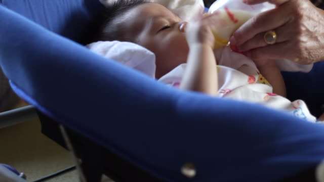 baby bottle feeding close up by grand father - milk bottle stock videos & royalty-free footage