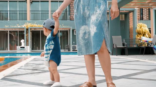 vídeos de stock, filmes e b-roll de menino e sua mãe curtindo e passando um tempo na praia - 6 11 months