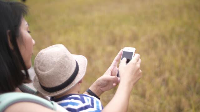 男の子の赤ちゃんと母親が携帯電話を使用して - 帽子点の映像素材/bロール
