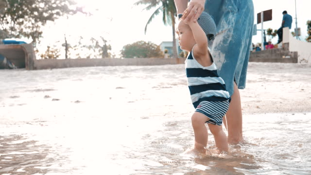baby junge und seine mutter zu fuß am strand - 6 11 months stock-videos und b-roll-filmmaterial