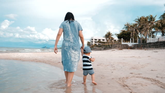 baby boy and his mother walking on the beach - toddler stock videos & royalty-free footage