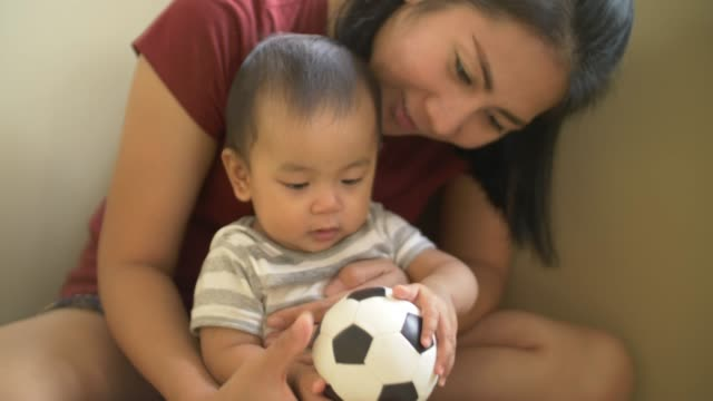 baby boy and mother are playing with soccer ball - crawling stock videos & royalty-free footage